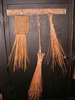 set of three pine needle brushes on lath peg rack